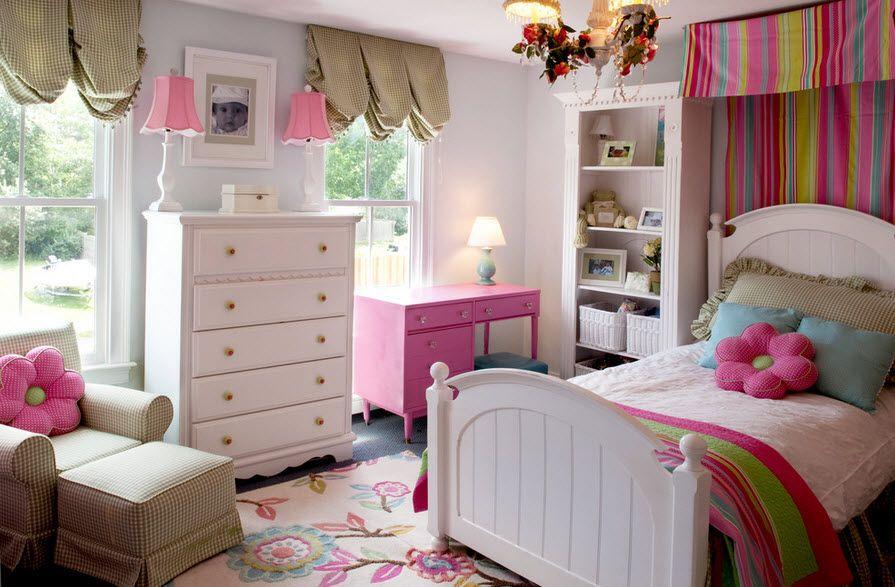 Детская комната с двумя окнами, комодом и кроватью в белых тонах