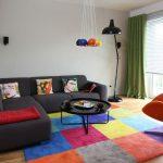 Яркий ковёр и тёмный диван в гостиной