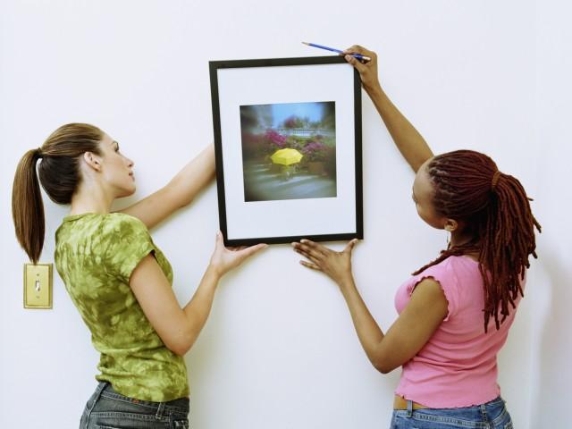 Девушки вешают картину на стену