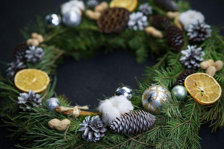 Рождественский венок из еловых веток с шишками, игрушками и сушеными лимонами