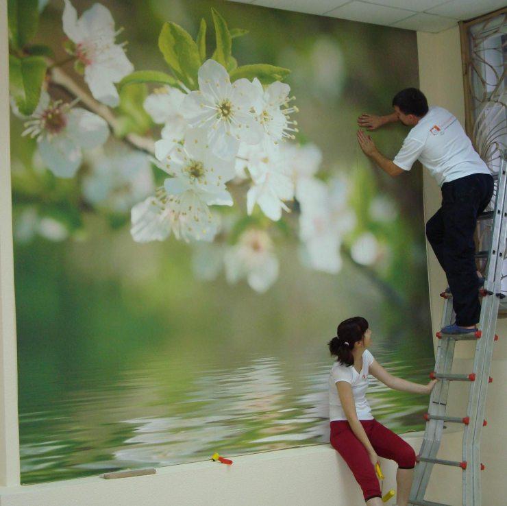 Мужчина и женщина клеют фотообои