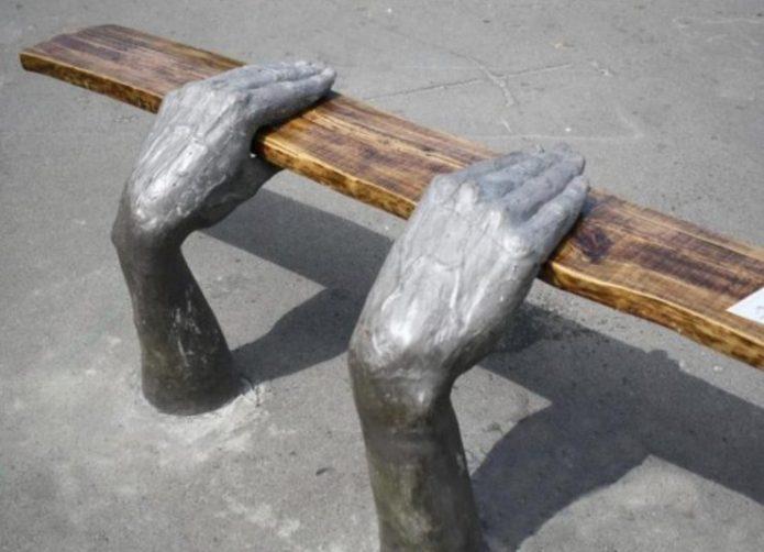 Скамья из деревянной доски и опор в виде рук