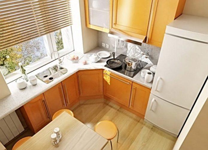 Маленькая кухня со столешницей у окна и оранжевой мебелью