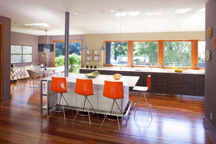 Большая кухня с коричневым ламинатом на полу