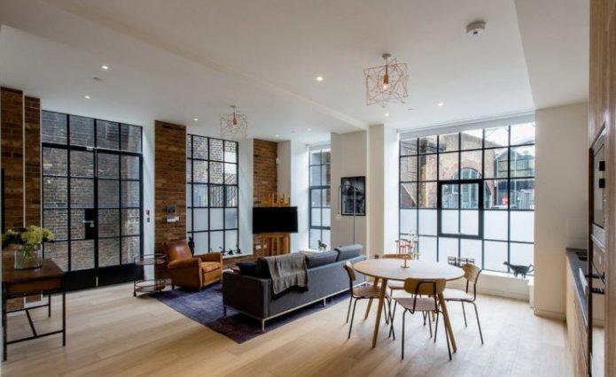 Светлый ламинат в интерьере просторной гостиной с панорамными окнами