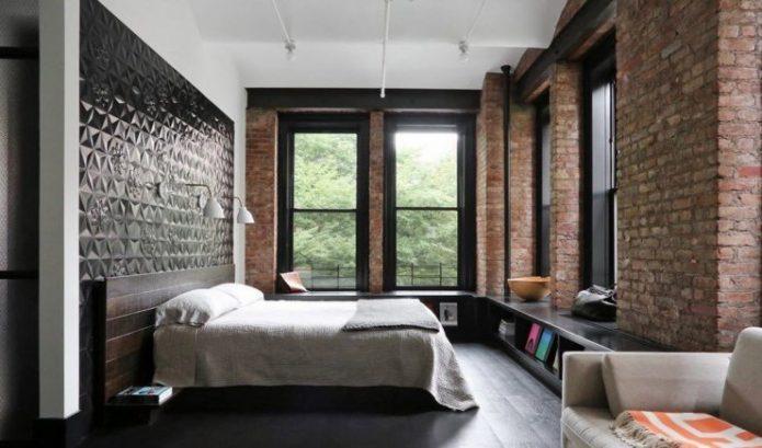 Спальня в темных оттенках с кирпичной стеной и темным ламинатом на полу