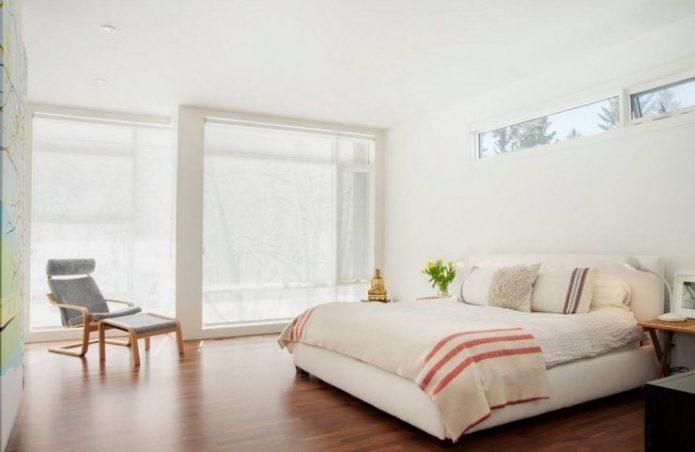 Спальня в нейтральных оттенках с коричневым ламинатом на полу