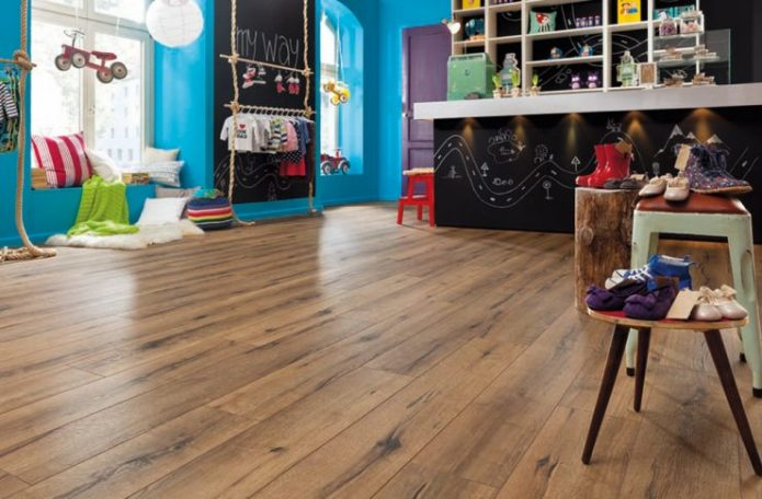 Просторная детская комната с коричневым ламинатом на полу
